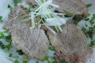 Xếp bánh phở, thịt bò vào bát và rắc rau thơm lên trên cùng